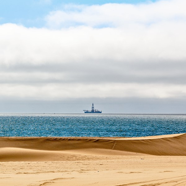Desert and seaside with offshore oil rigs